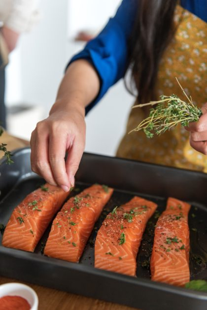 salmon on sheet pan with herbs on top