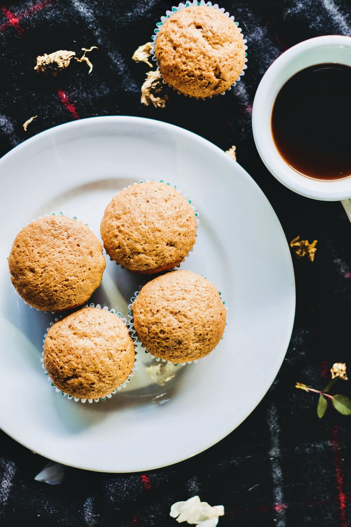 4 muffins on a white plate with cup of coffee