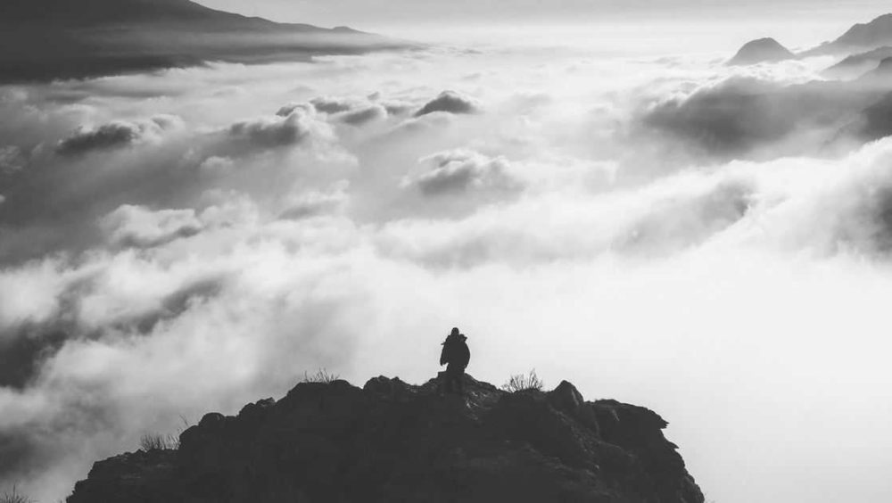 woman standing on side of a mountain looking at clouds