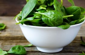 Fresh spinach in a white bowl on wooden table