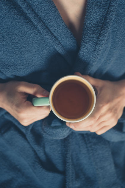 woman in blue robe drinking a cup of tea